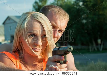 Young Man Is Teaching His Girlfriend To Shoot By Pneumatic Handgun.
