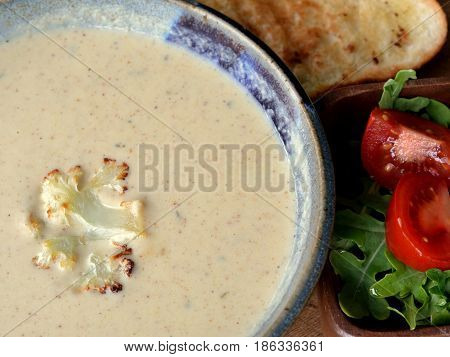 Roasted Cauliflower Soup: Close up of soup in a bowl served with bread and salad. Viewed from above.