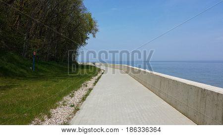 Seaside boulevard between trees and the sea, no people