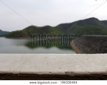 Looking over a white concrete fence with water in the dam,White wall texture background,Empty space for text.