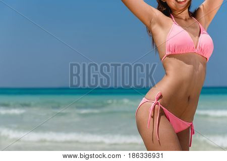 Sexy bikini body woman sun tanning relaxing on perfect tropical beach and turquoise ocean water. Unrecognizable model walking in fashion swimwear with smooth tanned skin and long lean legs. poster