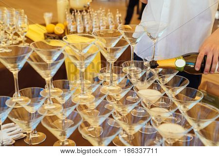 Pyramid Of Glasses Champagne On Wedding Party. Champagne Glass Pyramidю Male Bartender Pouring Champ