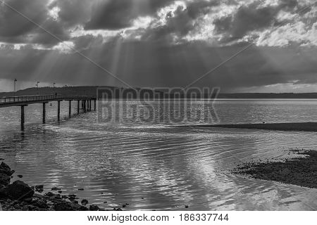 Rays of sunlight break through the clouds over the pier at Des Moines Washington. Black and white image.