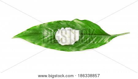 Shea butter on green leaf on white background