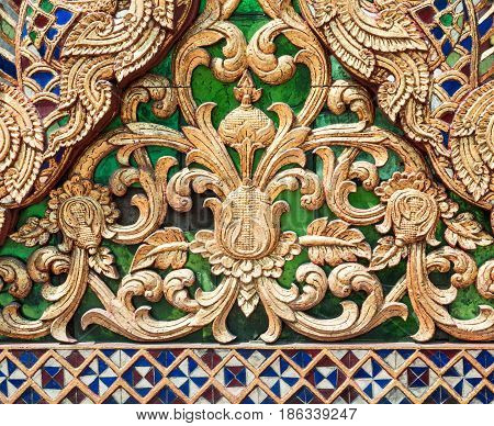Sculptured wood with the golden paint in the traditional Thai style on the triangle gable of the Thai church.