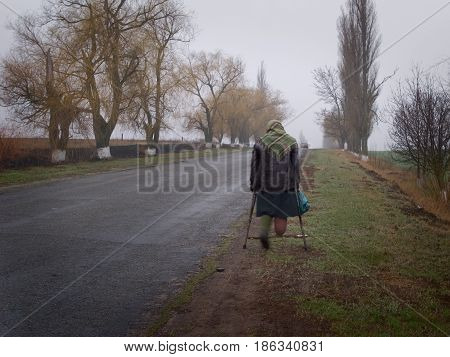 Spring. A lonely old woman goes on crutches on the road. Photographed in the Cherkassy region. Ukraine. Date / Time: 2004-04-08 05:47:04