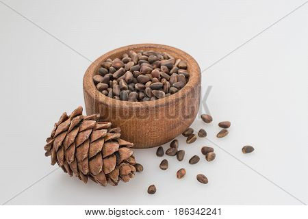 Cedar cones and a small wooden bowl with nuts on a light background.
