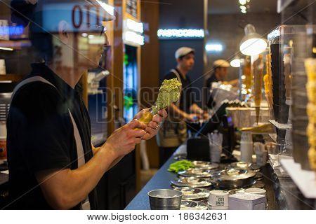 MILAN ITALY - FEBRUARY 26: View of Italian ice-cream maker prepares ice cream cones on february 26 2017