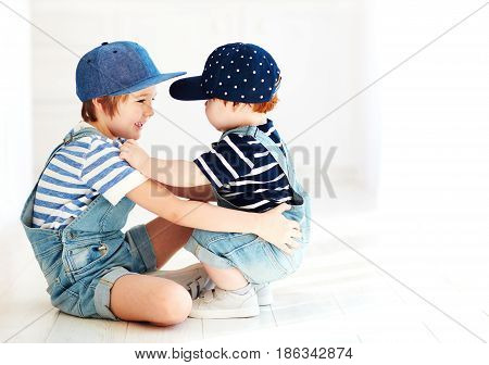 cute kids brothers in denim jumpsuits communicating indoors