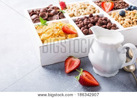 Milk jug and variety of cold quick breakfast cereals with berries in white wooden box, healthy eating for kids, selective focus, copy space.