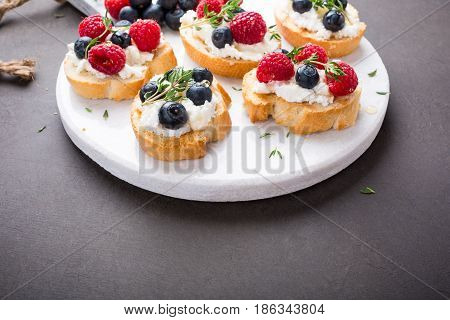 Sandwiches with fresh berries, goat cheese and honey on marble cutting board, copy space.