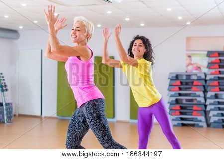 Happy female athletes doing aerobics exercises or Zumba dance workout to lose weight during group classes in fitness center.
