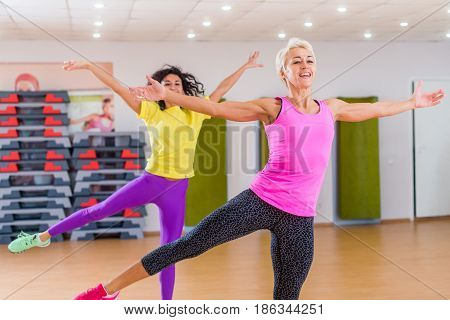 Two smiling athletic women doing aerobic dancing exercises holding their arms sideward indoors in fitness center