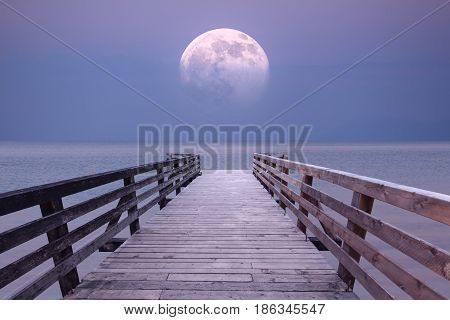 Super moon from wooden boardwalk on the beach in romantic ocean atmosphere. Fantasy concept.