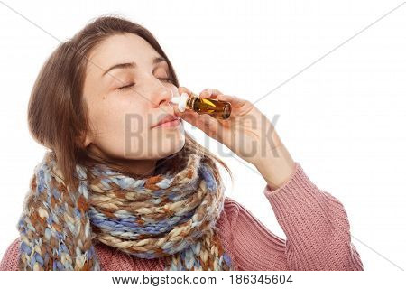 Young female in scarf using nasal drops on white background.