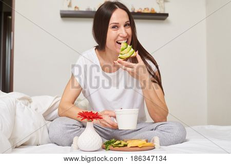 Mid shot of woman in pajamas drinking tea and eating sandwich with cheese, avocado sitting in the bed with copy space