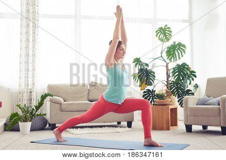 Wide shot of well-built female practicing yoga posture on yoga mat