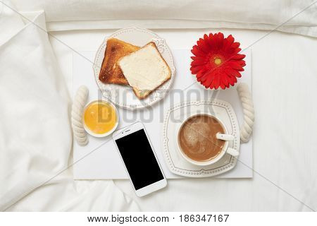 Top view of tasty breakfast on tray with telephone. Toasts, honey, coffee decorated with flower on tray