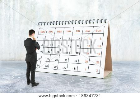 Thoughtful young businessman looking at calendar placed on concrete surface. Schedule concept. 3D Rendering