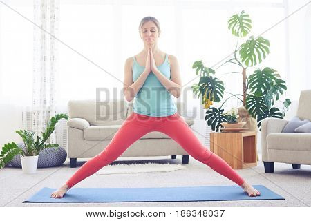 Wide shot of good-looking female in fashionable sportswear strengthening her body with yoga
