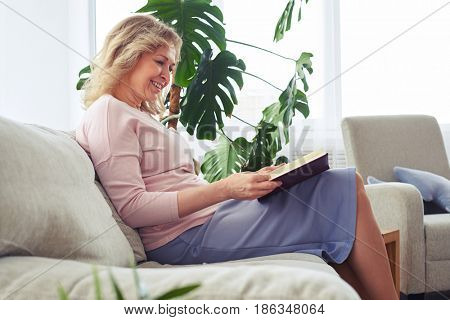 Mid shot of graceful adult woman smiling while reading book