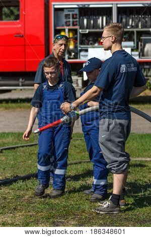 BERLIN - JUNE 11 2016: Berlin firefighter shows a group of children skills of working with fog nozzle. German-Russian festival devoted to the Independence Day of Russia. District Karlshorst East Berlin.