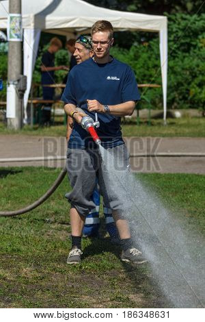 BERLIN - JUNE 11 2016: The Berlin firefighter shows skills of working with fog nozzle. German-Russian festival devoted to the Independence Day of Russia. District Karlshorst East Berlin.