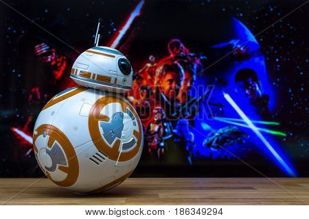 BERLIN GERMANY - JUNE 10 2016: BB-8 Android Models on the background of the official poster of the new movie of the saga Star Wars: The Force Awakens.