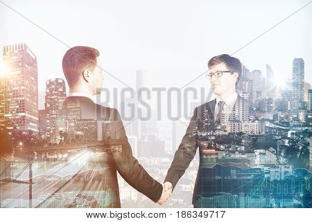 Attractive european businessmen shaking hands on abstract city background. Partnership concept. Double exposure