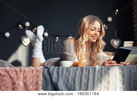 Cheerful pretty young girl lying on the bed and browsing the tablet. Horizontal indoors shot.