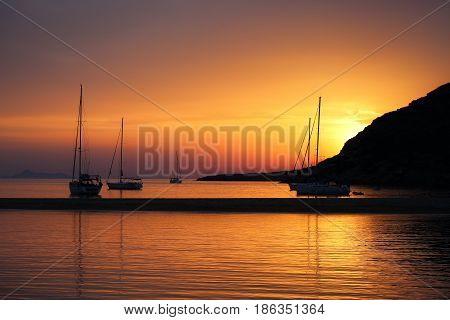 Fabulous Sunset in Kolona double bay Kythnos Cyclades Greece. Sailboats