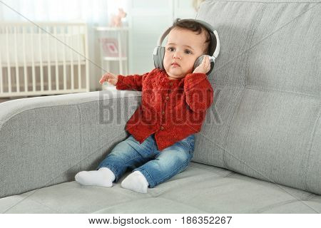 Cute little baby with headphones listening to music at home