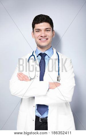 Handsome young doctor on light background