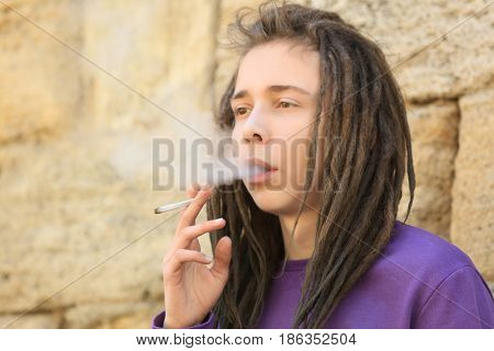 Young boy smoking weed on blurred background