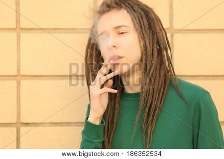 Young boy smoking weed on wall background