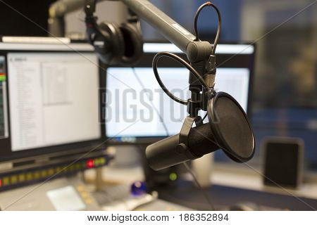 Studio microphone in front of a sound mixer and computers in broadcasting radio studio. New radio station studio.