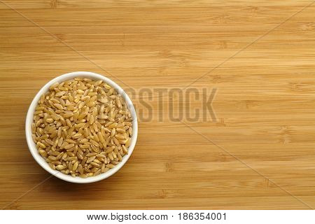 Cup of wheat on wood (Photo taken from top view)