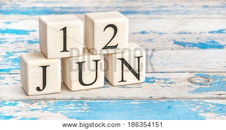 June 12th. Wooden cubes with date of 12 June on old blue wooden background.
