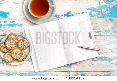 Notepad with cup of tea and saucer with cookies on the table. Top view.
