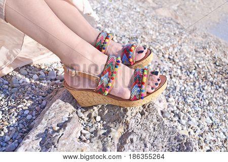 greek model advertises bohemian sandals on the beach