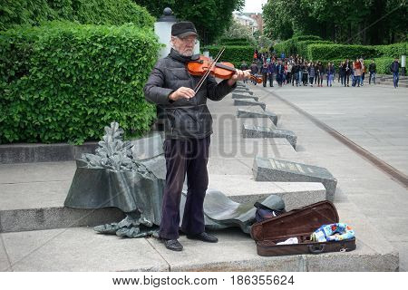 KIEV - UKRAINE - MAY 2017: Victory Day in Kiev. The pensioner plays the violin in the Glory Park. A group of students with flowers is passing him.