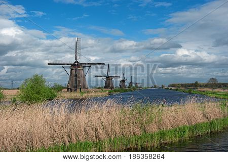 Traditional dutch windmills and water canal Kinderdijk Netherlands Benelux Europe. Typical old dutch mill scenery. Beautiful rural landscape. Famous village Kinderdijk. UNESCO world heritage site