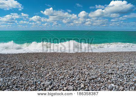 Beach blue sea cloudy sky. Beautiful landscape. Scenic view of ocean wave stones on sunny summer day. Seascape pebble beach Etretat Normandy France Europe. Popular landmark famous destination