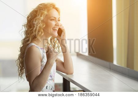 Euphoric Woman Searching Job In Cafe. Beautiful Girl Is Talking On The Phone And Happy With The Good