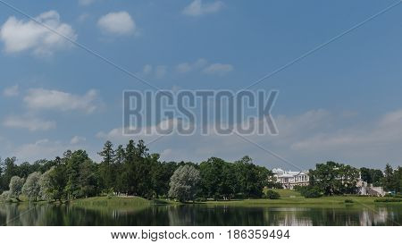 Beautiful Russian Landscape With Willows Near Water Of A Lake And Clouds In Blue Sky.