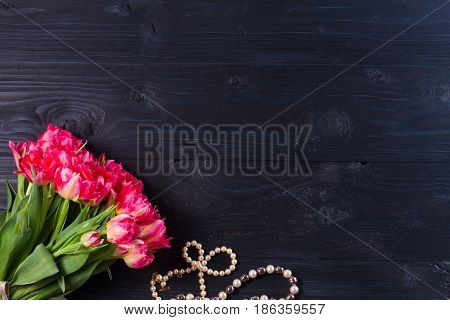 female flat lay scene fresh tulips flowers and jewellery on black wooden background