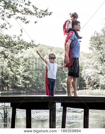 Happy loving family dad with two daughters plays a super hero in the open air near the river on the wooden pierthe concept of a super hero and a child's dreamsfather's Day