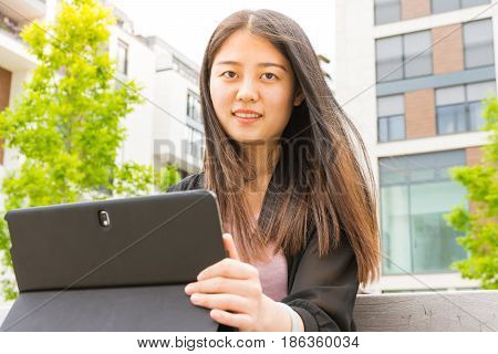 Attractive Asian Chinese Girl Sitting On Park Bench Working On Laptop Tablet Casual