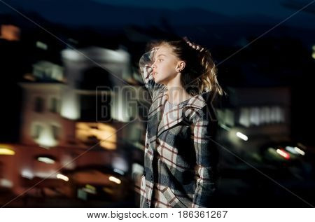 motion effect. night city with girl or woman blonde young model portrait in checkered coat motion effect