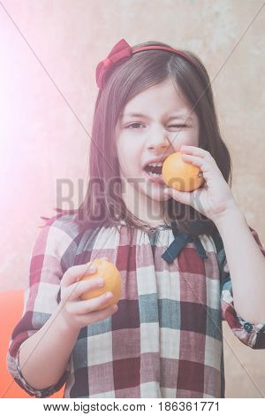 child small little girl with winking eye eating fresh vitamin yellow lemons citrus fruit with sour taste on beige wall. Light spot. Healthy food and vegetarian diet